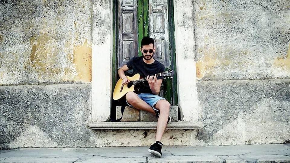 Osvaldo siede su un gradino, davanti ad una vecchia casa avente una porta verde, e indossa un paio di pantaloncini di jeans, una maglietta e scarpe nere, un paio di occhiali da sole e suona la sua chitarra