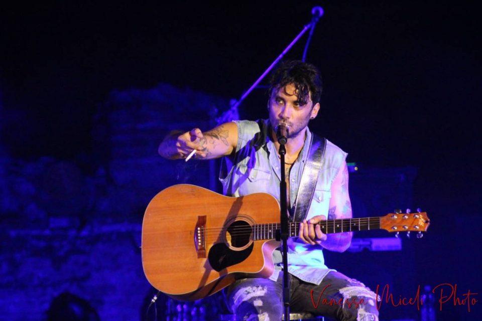 Fabrizio Moro imbraccia una chitarra e parla al suo pubblico fumando una sigaretta